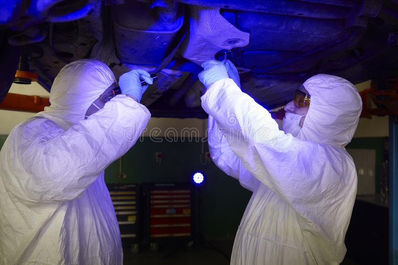 Police team working in ultraviolet light on collecting of traces and evidences royalty free stock photo