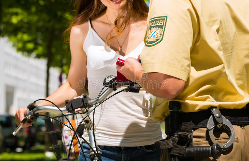 Police - woman on bicycle with police officer. Police - young woman on bicycle with police officer in traffic control stock photos