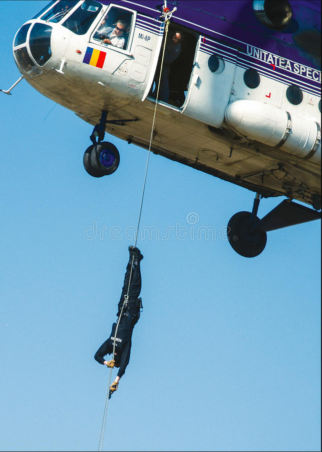 Policeman descending from helicopter royalty free stock images