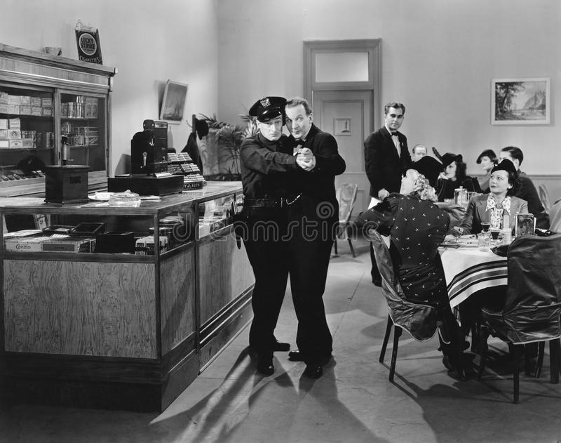 Policeman and a man dancing a tango in a restaurant. (All persons depicted are no longer living and no estate exists. Supplier grants that there will be no stock photos