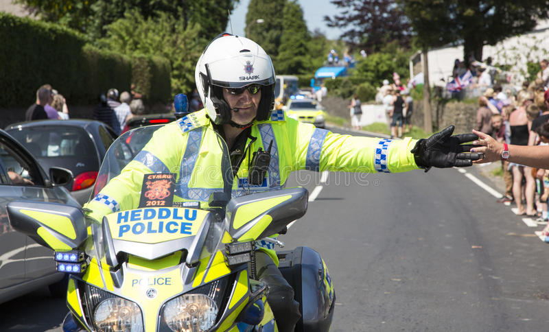 Policeman on motorbike. Olympic torch relay 26 May 2012 Bryncethin Bridgend UK Police man riding on a motorbike with hands outstretched to touch the crowds hands stock photo