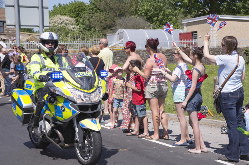 Policeman on motorbike. Olympic torch relay 26 May 2012 Bryncethin Bridgend UK Police man riding on a motorbike with hands outstretched to touch the crowds hands stock photography