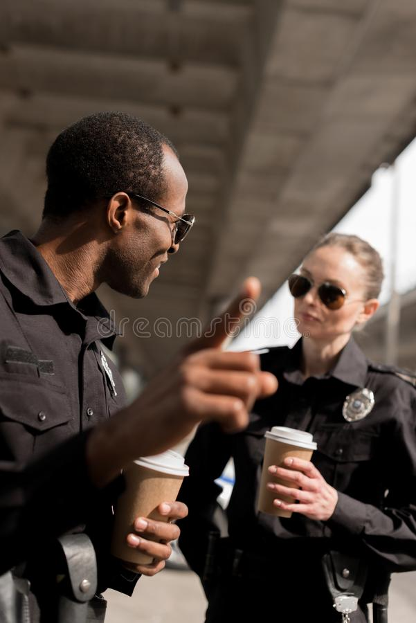 policeman pointing somewhere while drinking coffee to go royalty free stock photos