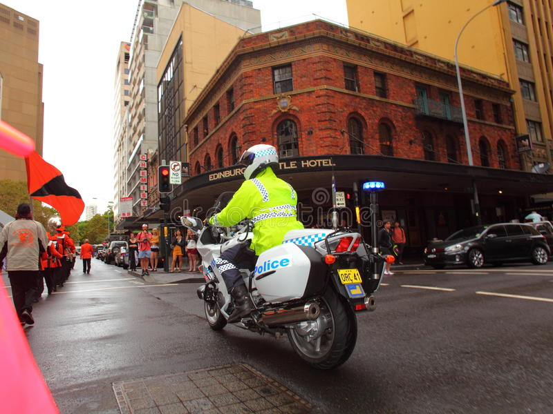Policeman on police motorbike. Policeman on motorbike guarding a parade through the city Sydney, Australia, at a rainy day. Street photography royalty free stock images