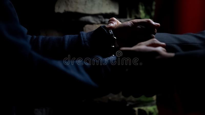 Policeman putting handcuffs on drug dealer in abandoned house, catching criminal royalty free stock photo