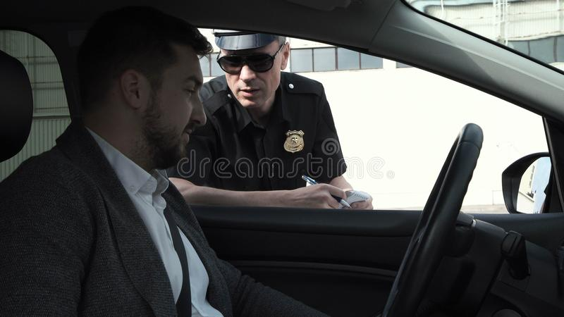Policeman stopping a driver royalty free stock photo