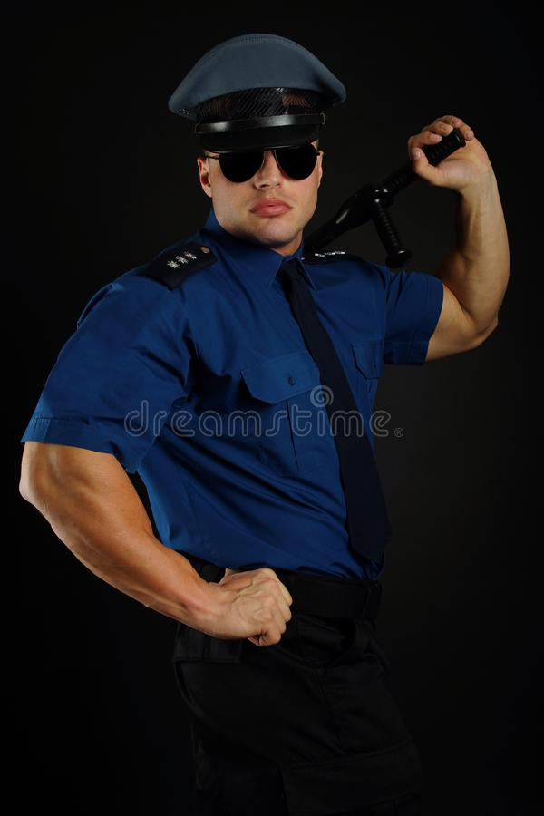 Policeman with sunglasses in uniform poses. royalty free stock images
