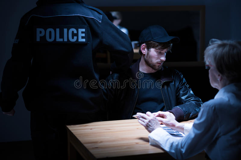 Policeman, suspect and female agent. Picture of policeman, young suspect and female police agent royalty free stock photography