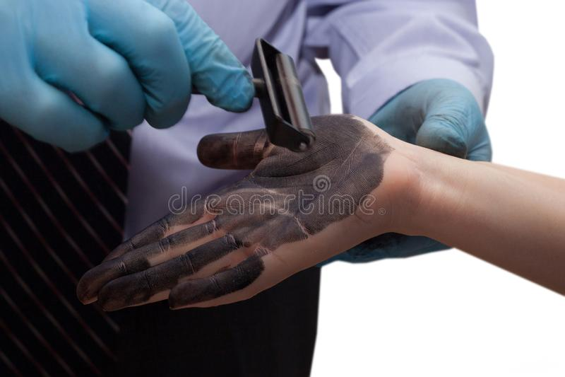 The policeman takes fingerprints from the suspect. Investigation of the crime stock photo