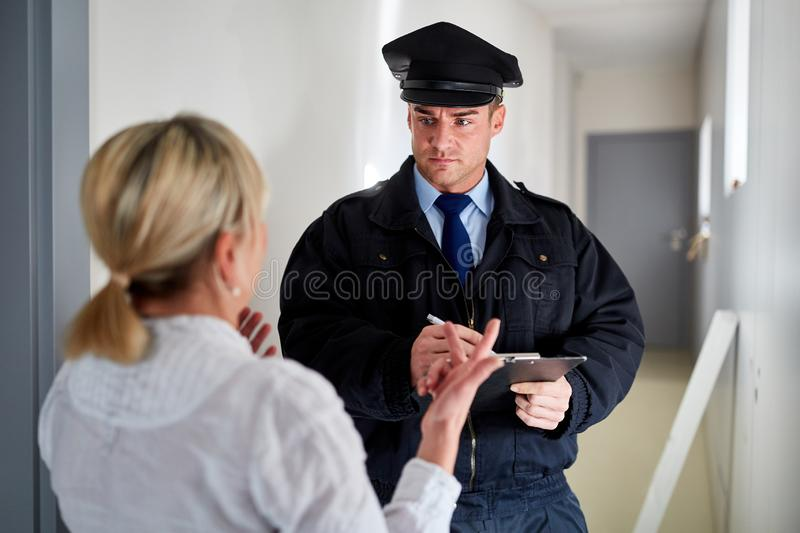 Policeman talks with wife at witness interview. Policeman talks to wife at witness interview at the front door after a burglary royalty free stock photos