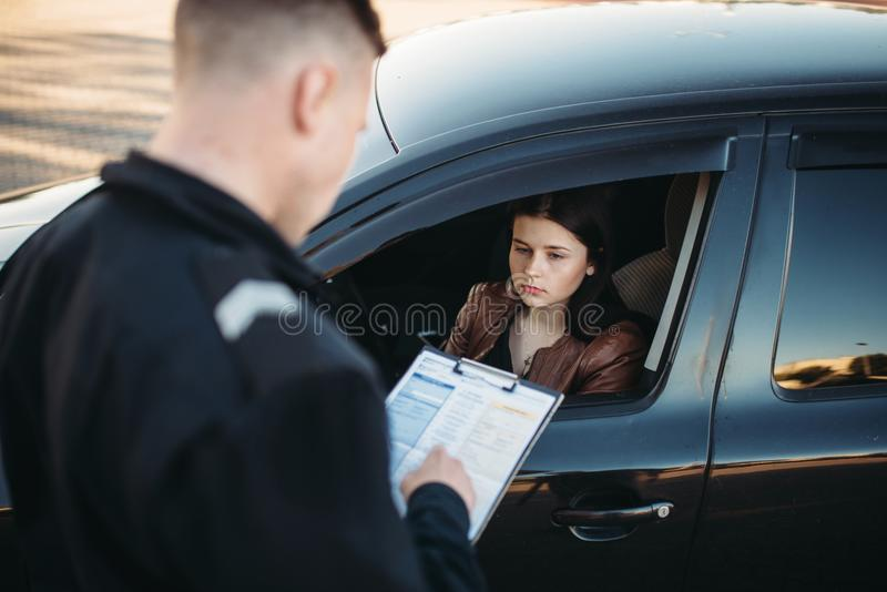 Policeman in uniform writes fine to female driver. Policeman in uniform writes a fine to female driver. Law protection, car traffic inspector, safety control job stock photos