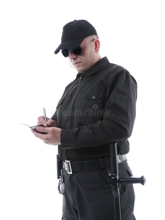 Policeman taking notes. Policeman wearing black uniform and glasses taking notes, shot on white stock image