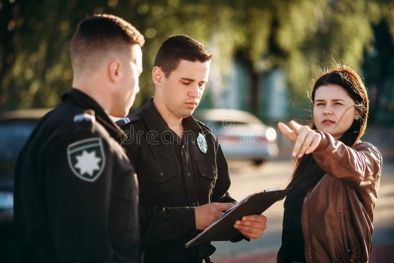 Policeman write testimony of female driver. Policeman in uniform write testimony of female driver. Law protection, car traffic inspector, safety control job royalty free stock photography