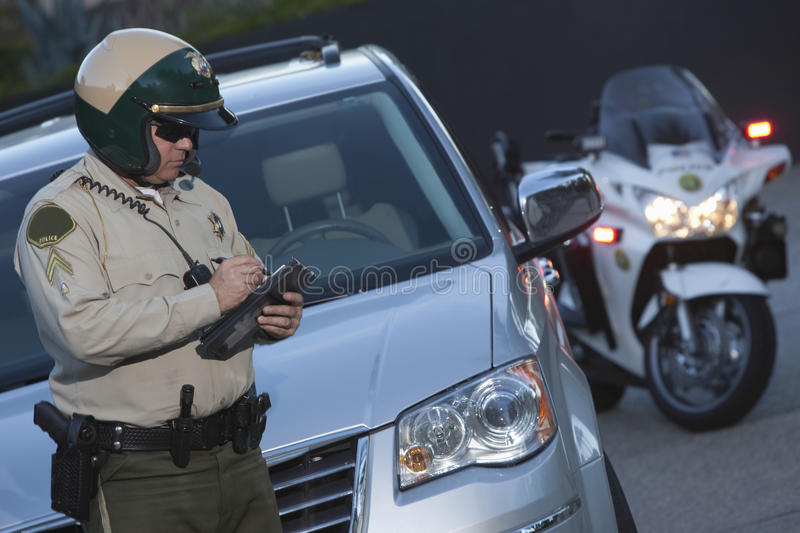 Policeman Writing Ticket While Standing In Front Of Car royalty free stock photo