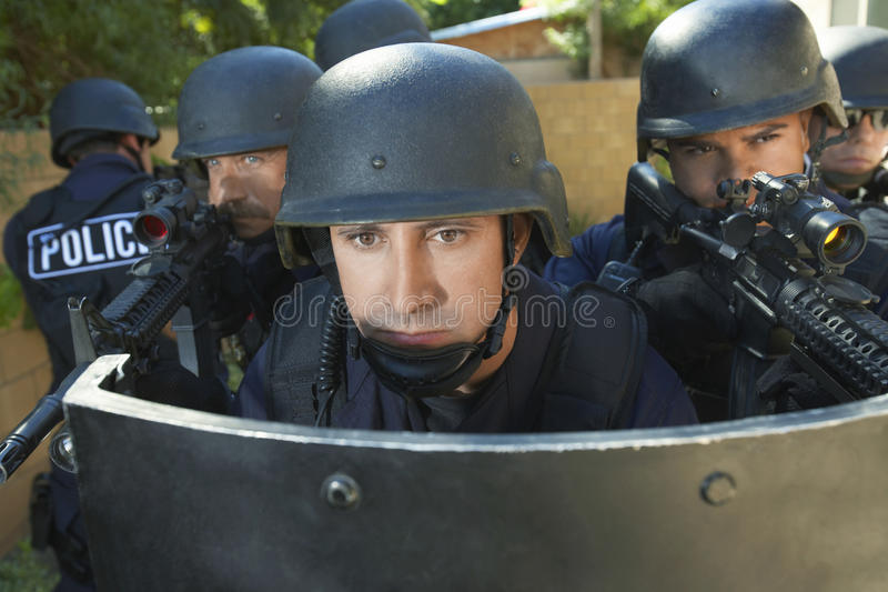 Policemen Aiming Guns While Standing Behind Shield stock images