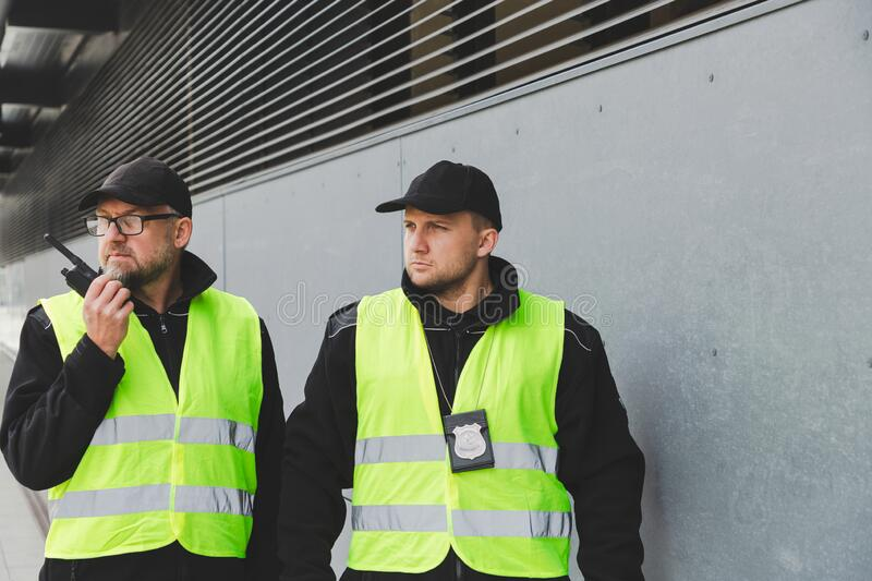 Policemen in vests looking around carefully during patrol in the city center. Policemen in reflective vests looking around carefully during patrol in the city royalty free stock photo