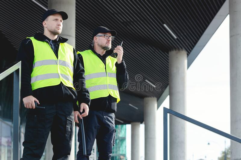 Reflective vests looking around carefully during patrol in the city center. Policemen in reflective vests looking around carefully during patrol in the city stock photography