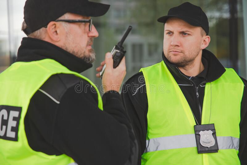 Close up of policemen speaking on the walkie-talkie during intervention stock images
