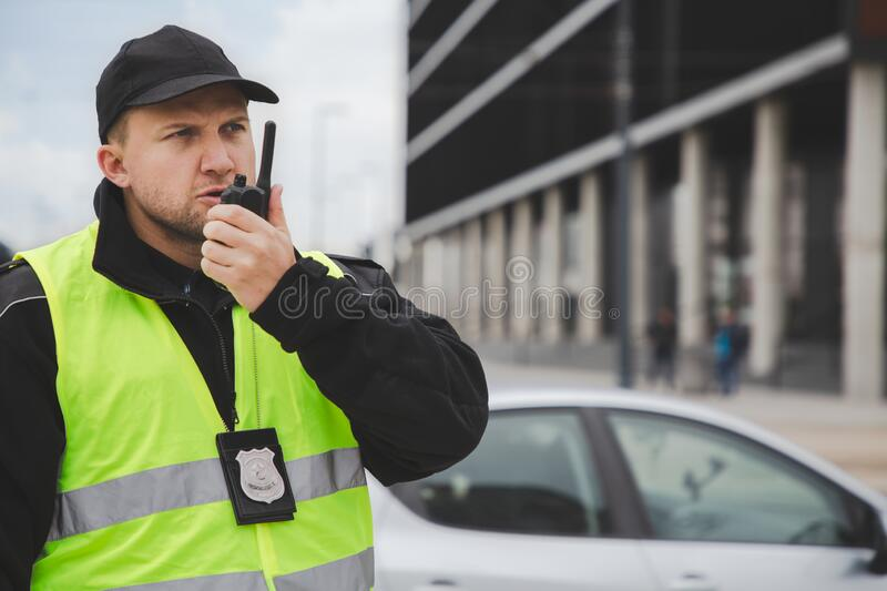 Policemen speaking on the walkie-talkie, reporting to station royalty free stock photos