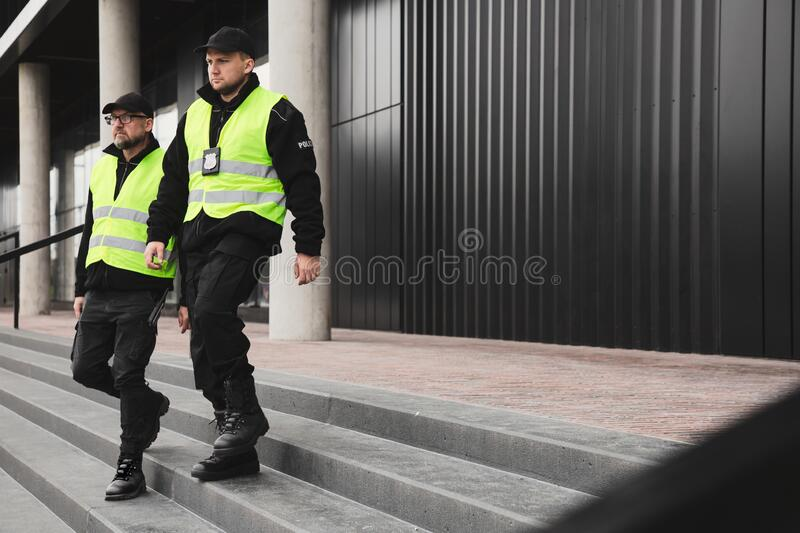 Policemen in vests looking around carefully during patrol in the city center royalty free stock photography