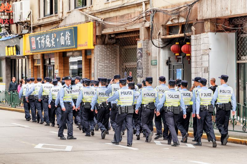 Policemen walking along street at downtown of Shanghai, China royalty free stock photos