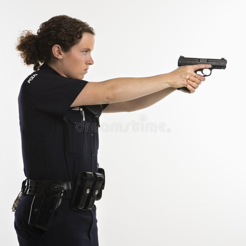 Policewoman aiming gun. Side view of mid adult Caucasian policewoman standing and aiming handgun with arms outstretched stock image