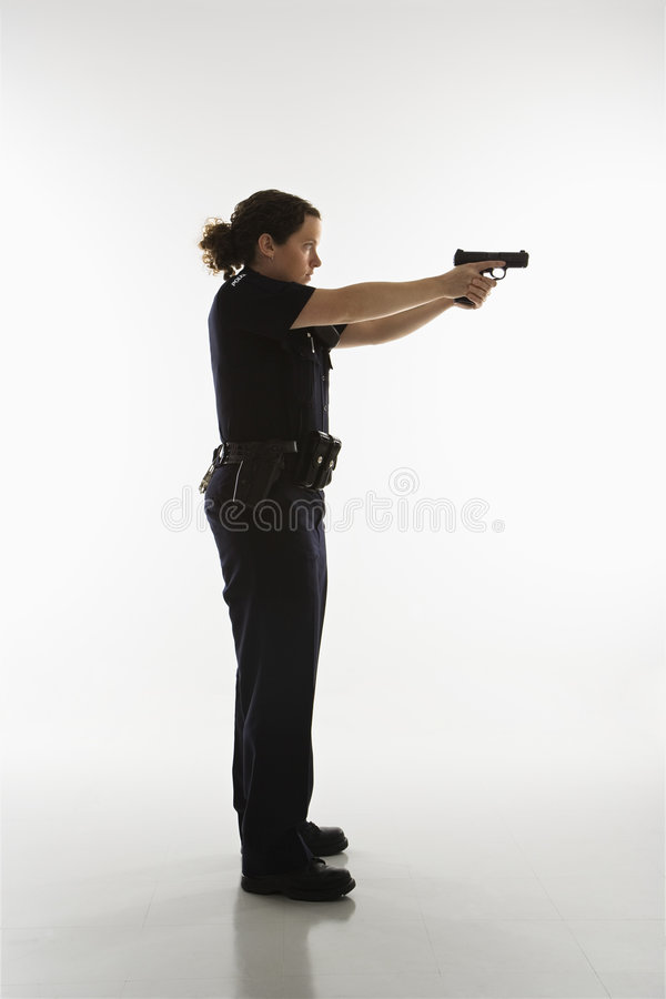 Policewoman aiming gun. Side view of mid adult Caucasian policewoman standing and aiming handgun stock images