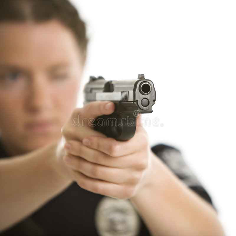 Policewoman aiming gun. Close up of mid adult female Caucasian law enforcement officer aiming gun at viewer with one eye closed royalty free stock images