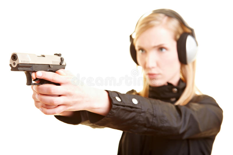 Policewoman exercising shooting. Young female shooter with pistol and ear protection stock photography