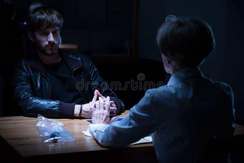 Policewoman interrogating young criminal stock photo