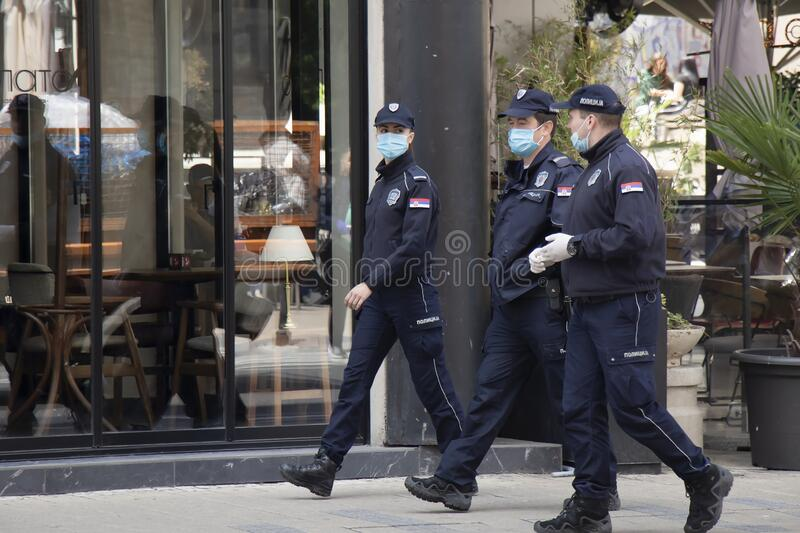 Policewoman and policemen on duty, wearing surgical face masks while walking city street royalty free stock photo