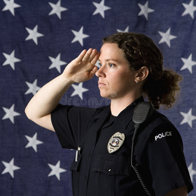 Policewoman saluting. Portrait of mid adult Caucasian policewoman saluting with American flag as backdrop stock images