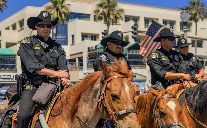 Policiais equestres da praia de Huntington e dos departamentos de polícia de Santa Ana em frente ao cais de praia de Huntington imagem de stock