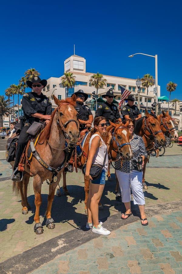 Policiais equestres da praia de Huntington e dos departamentos de polícia de Santa Ana em frente ao cais de praia de Huntington fotos de stock royalty free
