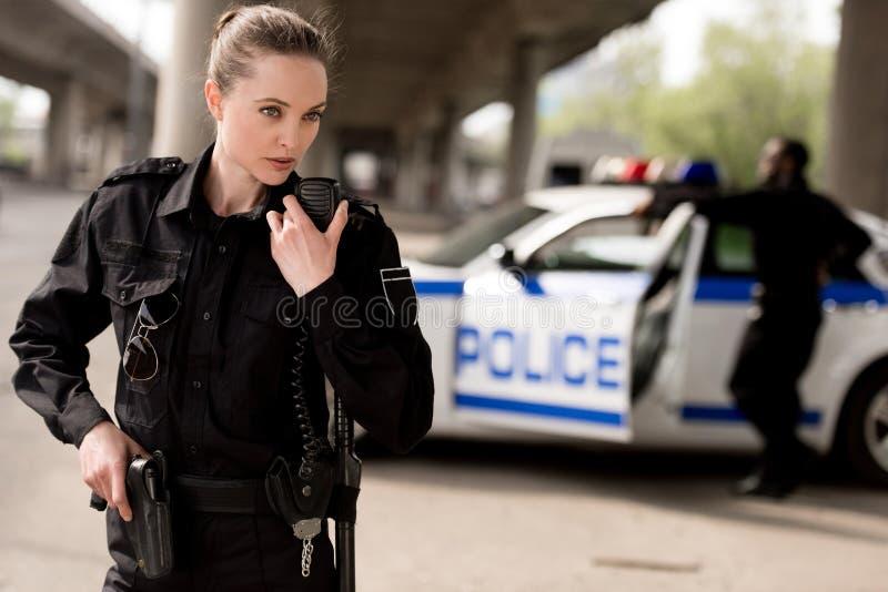policial atrativa nova que usa o Walkietalkie com o sócio borrado perto do carro fotos de stock
