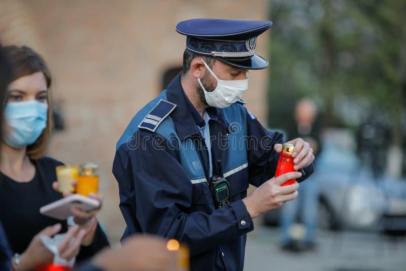 Policial romeno com máscara cirúrgica devido à pandemia de 19-2010 leva a Santa Luz durante a Páscoa ortodoxa imagem de stock