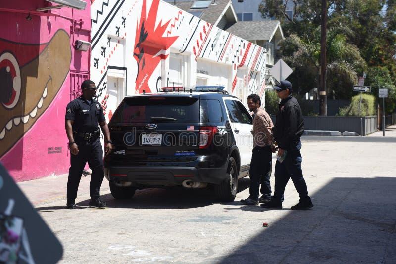 Policie a apreensão de homem novo não identificado na praia de Veneza, CA imagem de stock royalty free