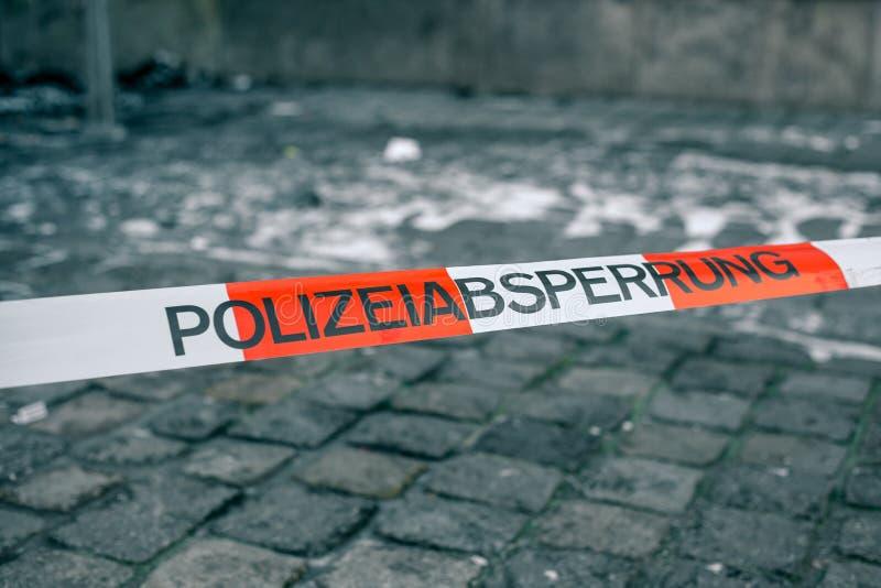 Policie a fita em Alemanha na cena do crime com a inscrição no cordão alemão da polícia Cena criminosa fotos de stock royalty free