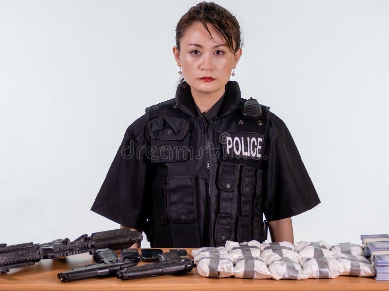 Policier asiatique féminin avec les marchandises saisies photographie stock