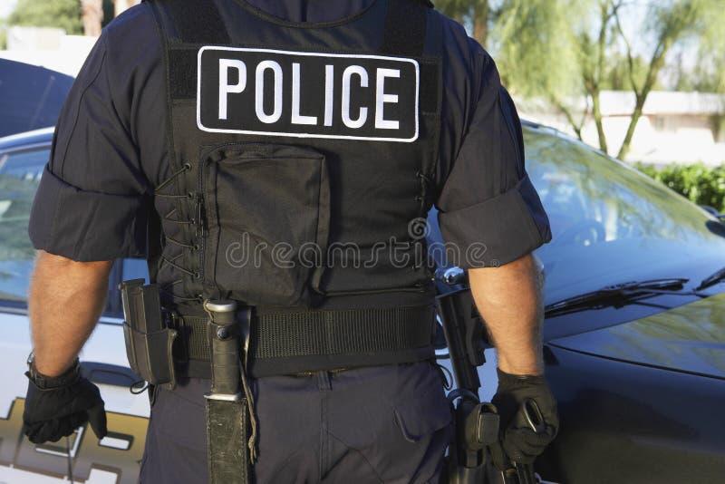 Policier dans l'uniforme se tenant contre la voiture image libre de droits