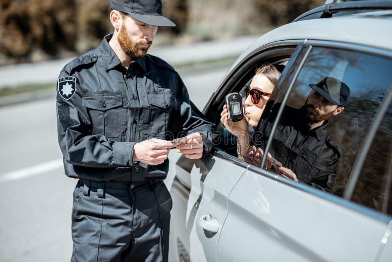 Policier examinant le conducteur de femme pour assurer l'intoxication d'alcool photos libres de droits