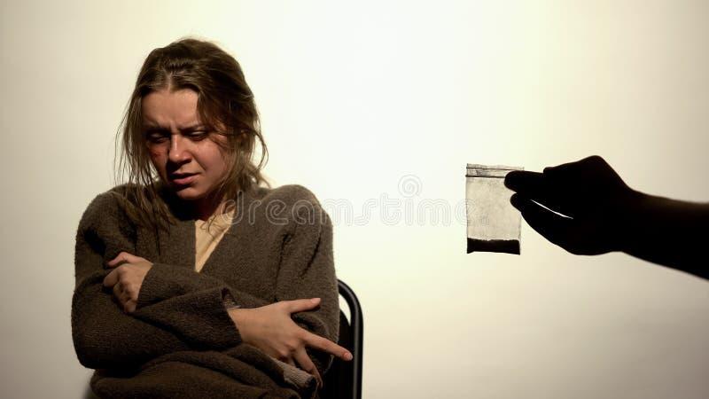 Policier montrant la femme pleurante de paquet de drogues, preuves psychical, enquête photographie stock