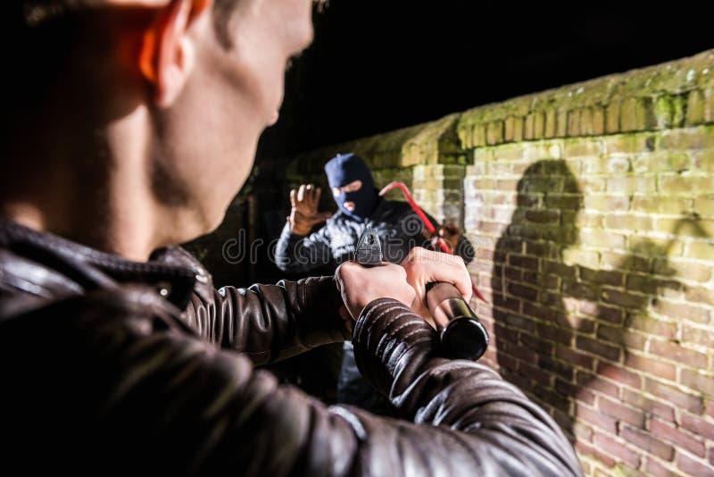 Policier visant la torche et l'arme à feu vers le burgla effrayé éclaté images libres de droits