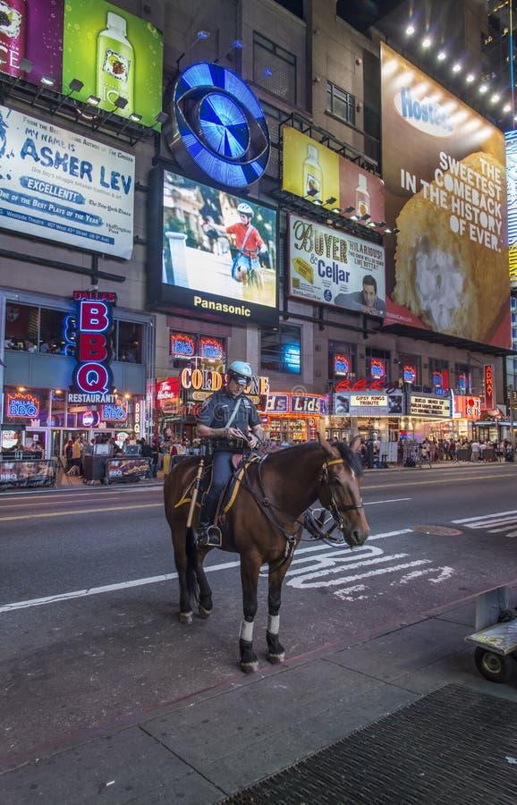 Policiers montés de NYPD sur des chevaux dans le Times Square la nuit, l'emplacement célèbre à New York City photo libre de droits