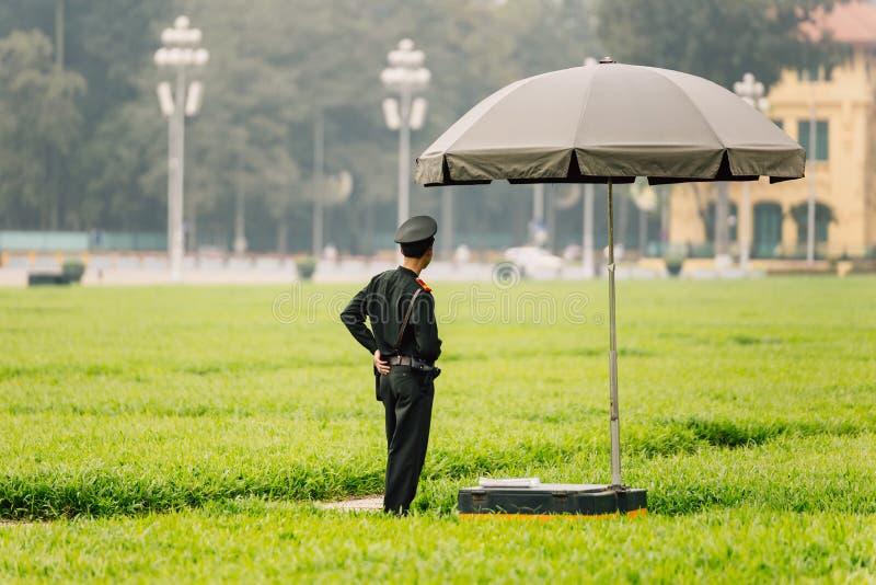 Policiers vietnamiens se tenant sous le parapluie sur le champ vert devant Ho Chi Minh Mausoleum à Hanoï, Vietnam photo stock