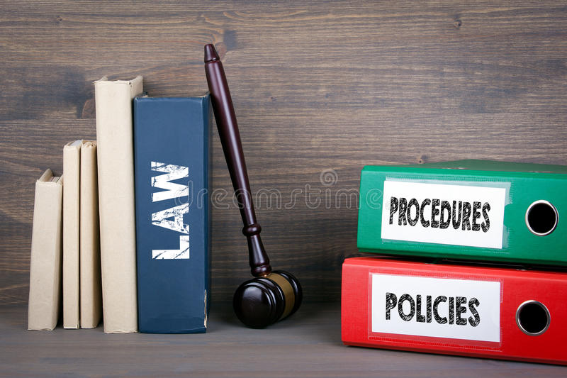 Policies and Procedures concept. Wooden gavel and books in background royalty free stock photography