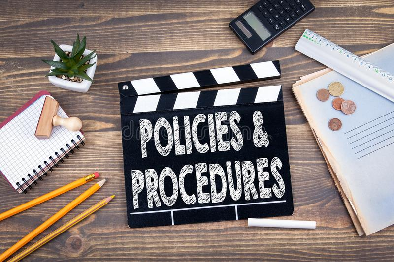 Policies and Procedures. movie clapper on a wooden desk stock image