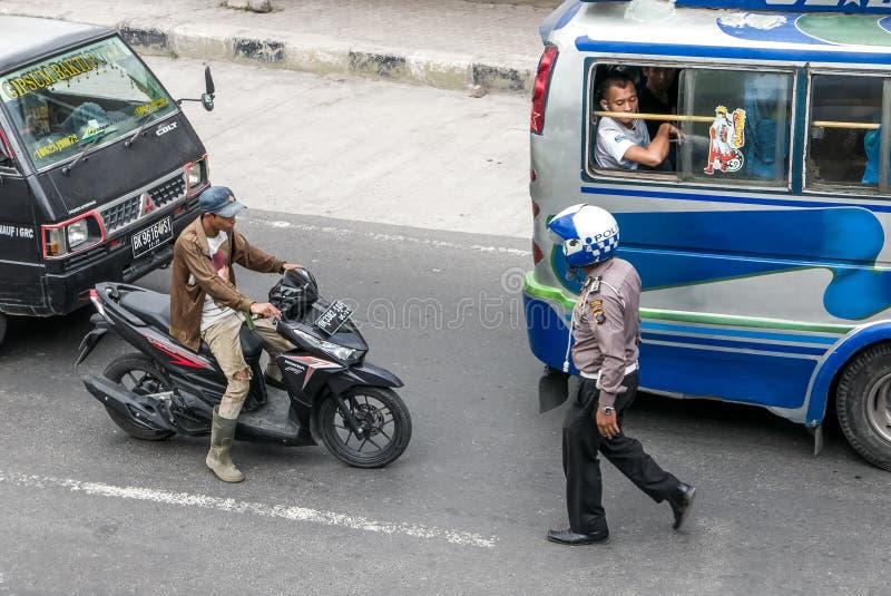 Policjant zbliża się rowerzysty na ruchliwej ulicie w Sumatra obrazy stock