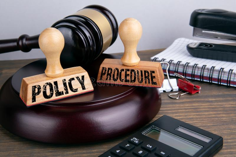 Policy and Procedure concept. Judge gavel and stationery. On a wooden table stock image