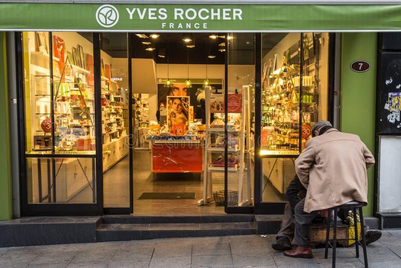 Polierschuhe Shoeshiner vor dem lokalen Yves Rocher-Speicher mit seinem Zeichen Yves Rocher ist eine französische Kosmetikmarke stockbilder